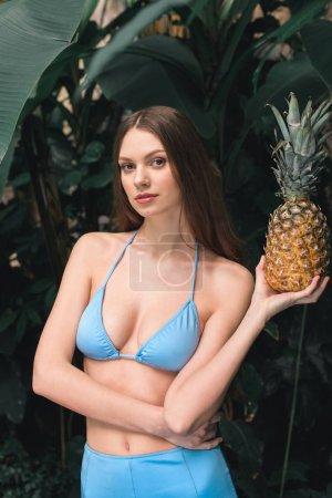 beautiful young woman in blue bikini holding pineapple on tropical resort