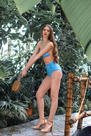 elegant woman in blue bikini posing with pineapple in tropical garden