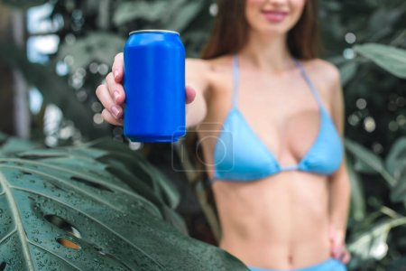 cropped view of girl in bikini showing blue soda can in tropical garden