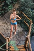 overhead view of beautiful girl in bikini posing with coconut cocktail on tropical resort