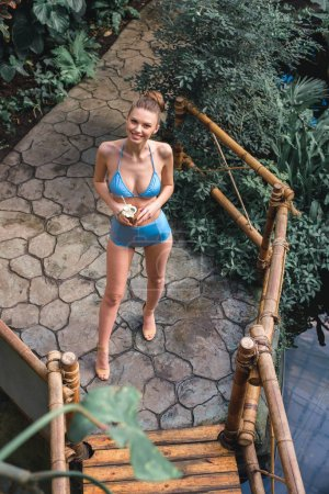 overhead view of beautiful smiling girl in bikini posing with coconut cocktail in tropical garden
