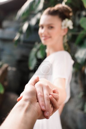 selective focus of woman in white dress holding hands with man