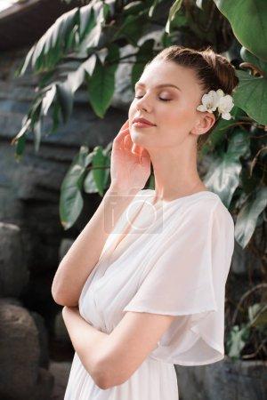 attractive tender bride posing in white dress in tropical garden