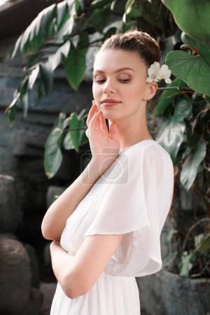 attractive bride in white dress with flower in hair posing in tropical garden