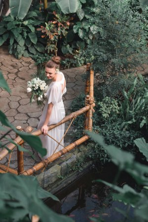 overhead view of attractive bride posing in white dress with wedding bouquet in tropical garden