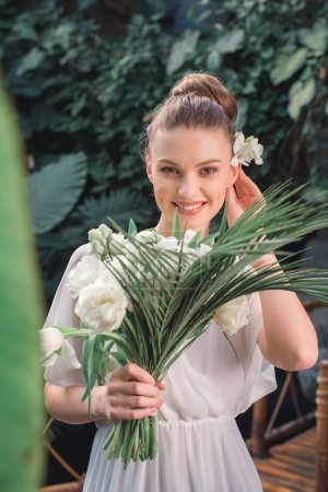 beautiful smiling bride posing in white dress with wedding bouquet in tropical garden