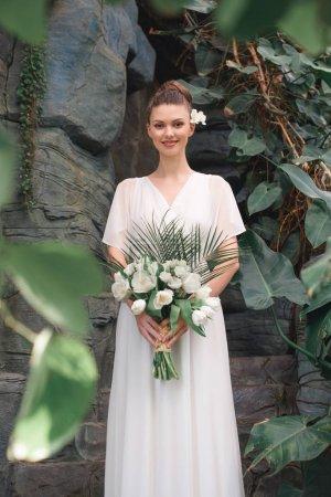 belle mariée heureuse posant dans une robe blanche avec bouquet de mariée