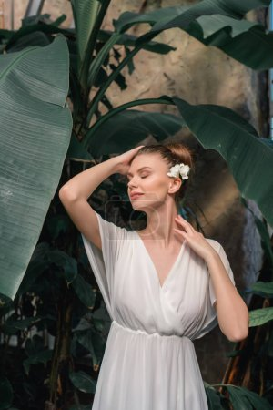tender woman in white dress with flower in hair posing in tropical garden