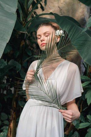 Photo pour Tendre jeune fille en robe d'été blanche posant avec des feuilles de palmiers tropicaux - image libre de droit