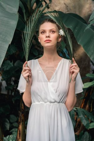 stylish girl in white summer dress posing with tropical palm leaves