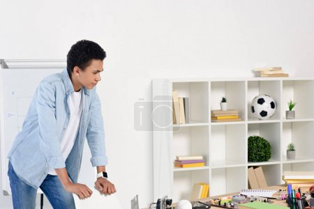 african american teenager leaning on chair and looking at table with technical equipment at home