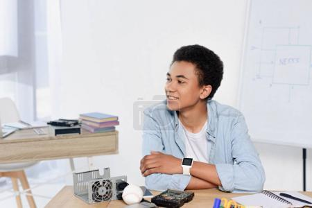 african american teenager sitting at table with technical equipment at home