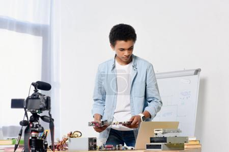 african american teenager preparing shooting tech video blog at home