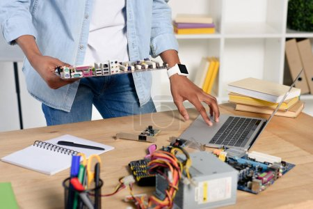 cropped image of african american teenager holding computer motherboard and using laptop at home