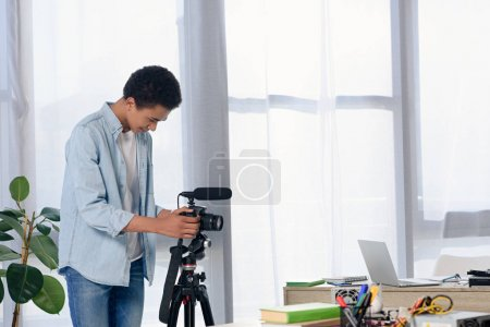 african american teenager setting camera for shooting video blog at home