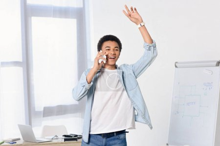 african american teenager talking by smartphone and waving hand at home