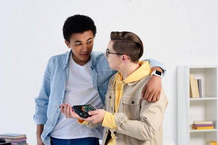 Foto de Chicos adolescentes multiculturales abrazando y fijación circuito de computadora en casa - Imagen libre de derechos