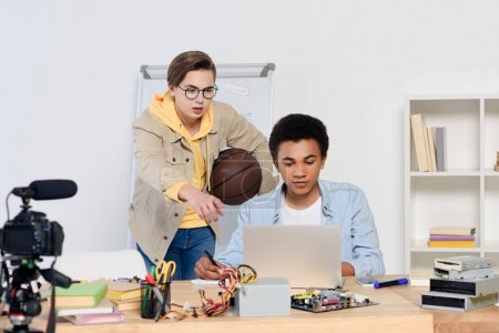 caucasian teenager pointing on something at laptop to african american friend at home
