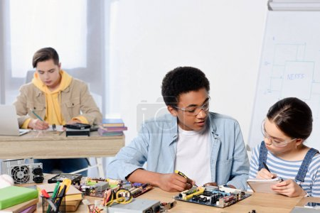 multicultural teenagers fixing computer motherboard at home