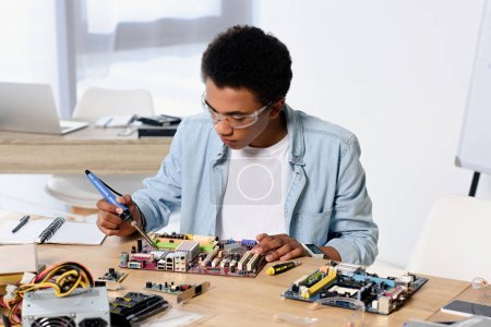 african american teenager soldering computer circuit with soldering iron at home