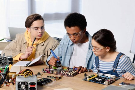 multicultural teenagers soldering computer circuit with soldering iron at home