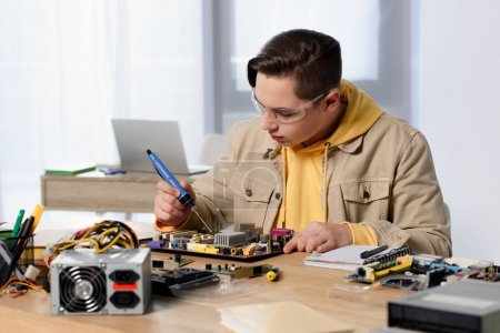 Photo for Teen boy soldering computer motherboard with soldering iron at home - Royalty Free Image