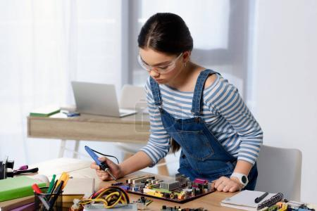 Photo for Female teenager soldering computer motherboard with soldering iron at home - Royalty Free Image
