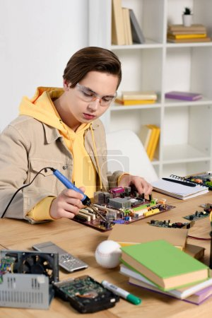 Photo for Teen boy soldering computer circuit with soldering iron at home - Royalty Free Image