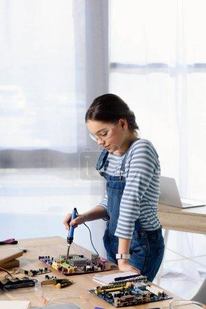 Photo pour Adolescent femelle souder circuit d'ordinateur avec fer à souder à la maison - image libre de droit