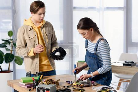 Photo for Teen boy watching how female teenager brazing computer circuit with soldering iron at home - Royalty Free Image