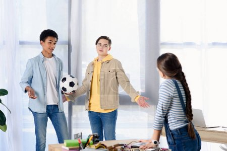 multicultural teenagers holding football ball and looking at friend at home