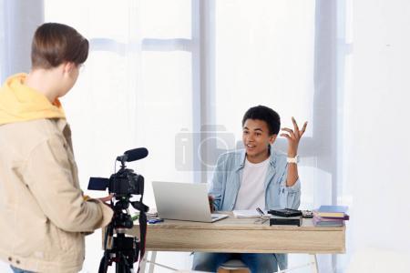 Photo pour Multiculturel adolescent garçons tir vidéo blog avec caméra à la maison - image libre de droit