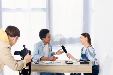caucasian teen kid conducting interview with african american friend for video blog