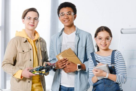multicultural teenagers holding computer motherboard and books at home