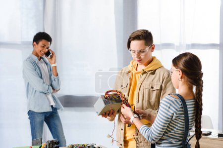 teenagers looking at computer power supply at home