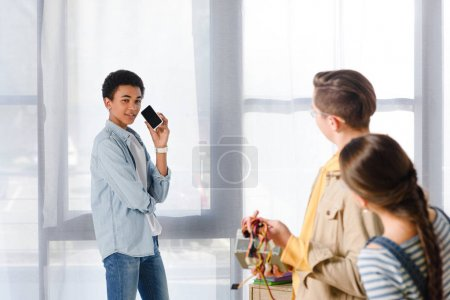 african american boy talking by smartphone and looking at friends at home