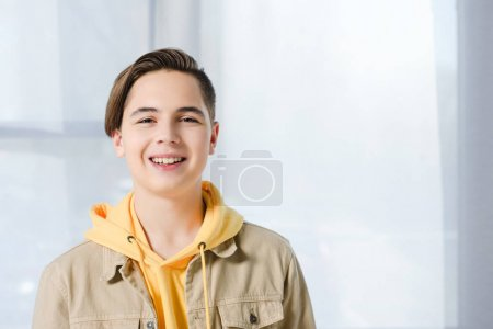 portrait of smiling teen boy looking at camera at home