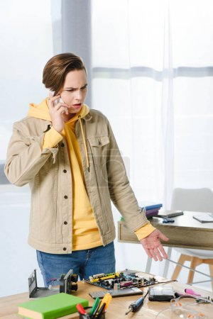 irritated teen boy talking by smartphone at home