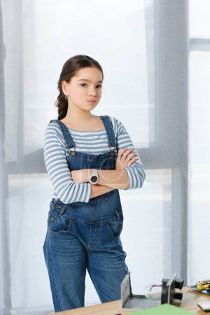 Photo for Preteen child standing with crossed arms and looking at camera at home - Royalty Free Image