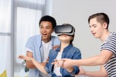 multicultural teenagers supporting friend with virtual reality headset at home