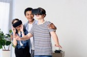 multicultural teenagers having fun with virtual reality headsets at home