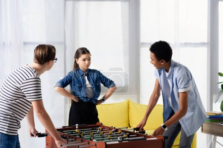 multicultural teen boys playing table football and female friend standing with hands akimbo at home