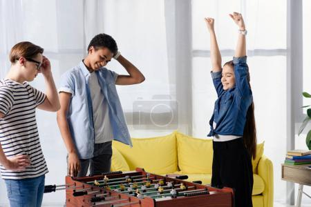 happy teen kid winning table football at multicultural teenagers at home