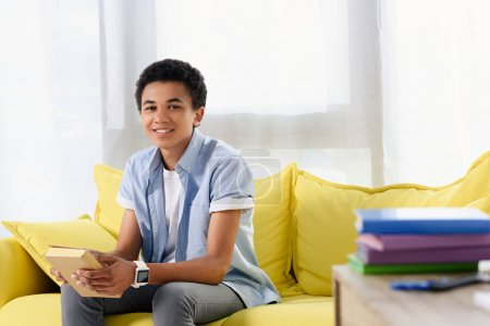 smiling african american teenager sitting with book on sofa at home