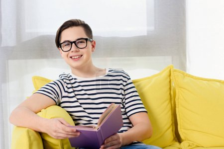 smiling teen boy sitting with violet book on yellow sofa at home