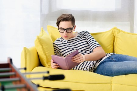 smiling teen boy reading violet book on yellow sofa at home