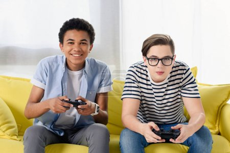 happy multicultural teen boys playing video game at home