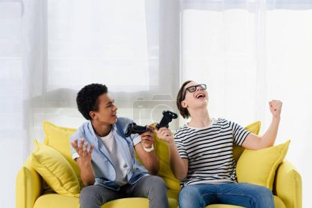 multicultural teen boys showing yes gestures when winning video game at home