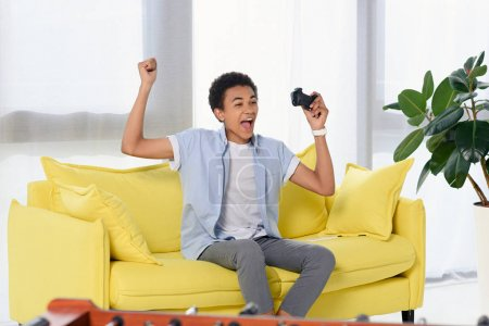 happy african american teenager winning video game and showing yes gesture at home