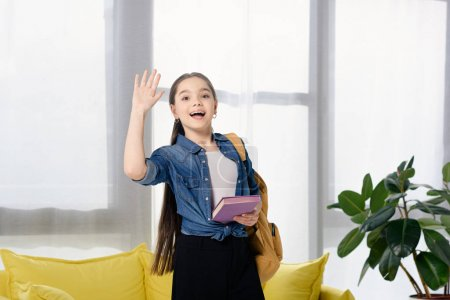 adorable preteen child waving hand at home
